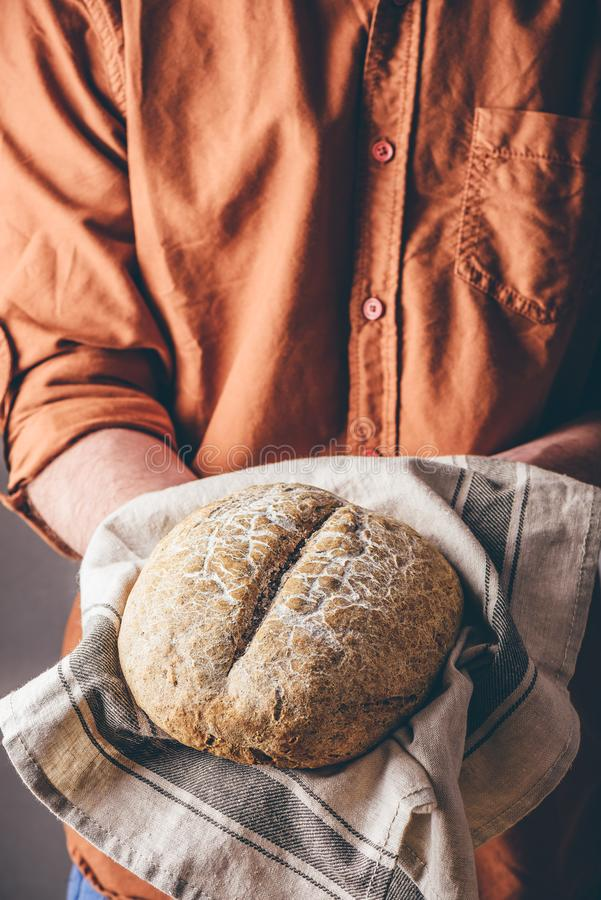 Man holds a freshly baked rye bread royalty free stock photo