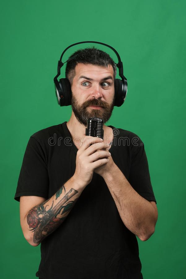 Man holds microphone on green background. Technologies and music concept. Dj with beard wears headphones. Singer with beard and shocked face listens to music royalty free stock images