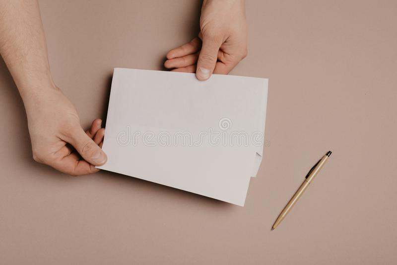 Man holds a mock-up letter or postcard in his hands with envelope on a gray background.  stock images