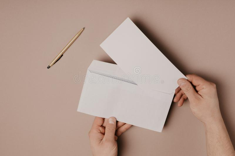 Man holds a mock-up letter or postcard in his hands with envelope on a gray background.  stock image