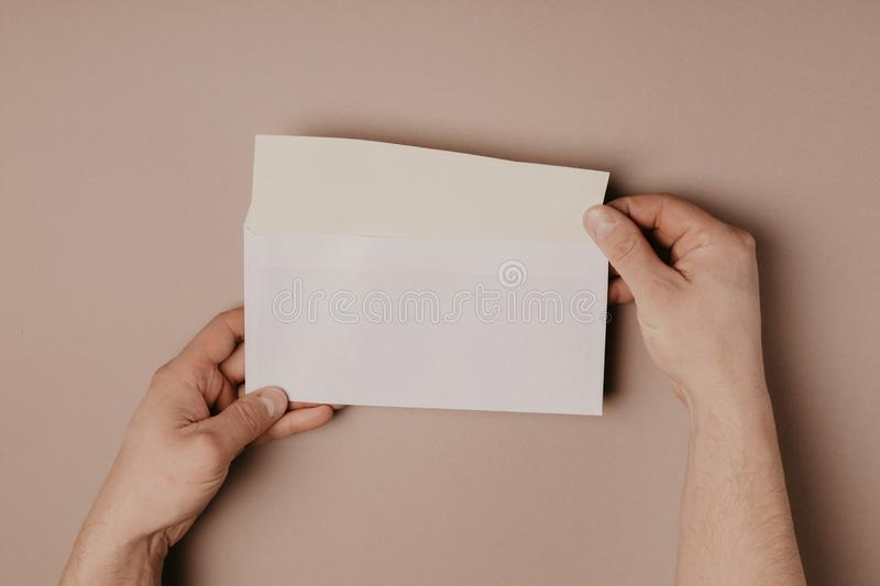 Man holds a mock-up letter or postcard in his hands with envelope on a gray background.  royalty free stock photos