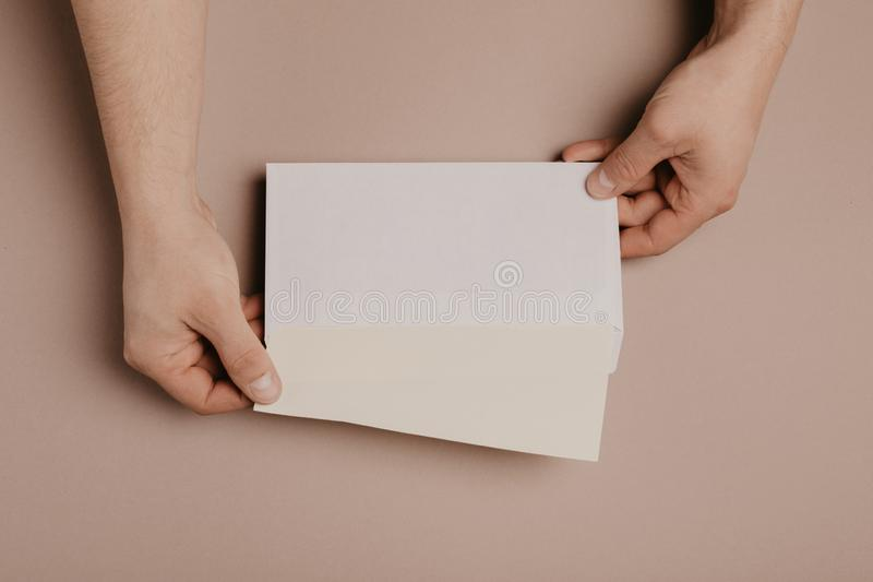 Man holds a mock-up letter or postcard in his hands with envelope on a gray background. Man holds a mock-up letter or postcard in his hands with envelope on a stock photos
