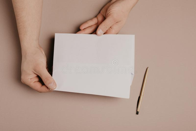 Man holds a mock-up letter or postcard in his hands with envelope on a gray background.  royalty free stock photography