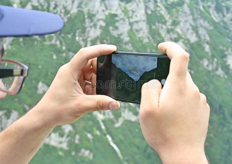 man holds a modern smartphone in his hands and takes pictures in the mountains royalty free stock photo