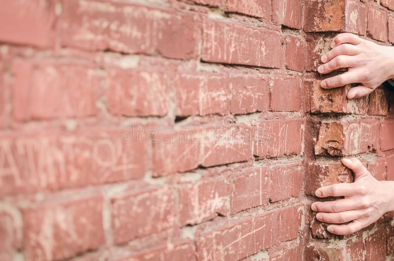 Fall. Man holds onto a ledge on a brick wall. A man holds onto a ledge on a brick wall so as not to fall down. The man climbs up. Person falling down royalty free stock photos