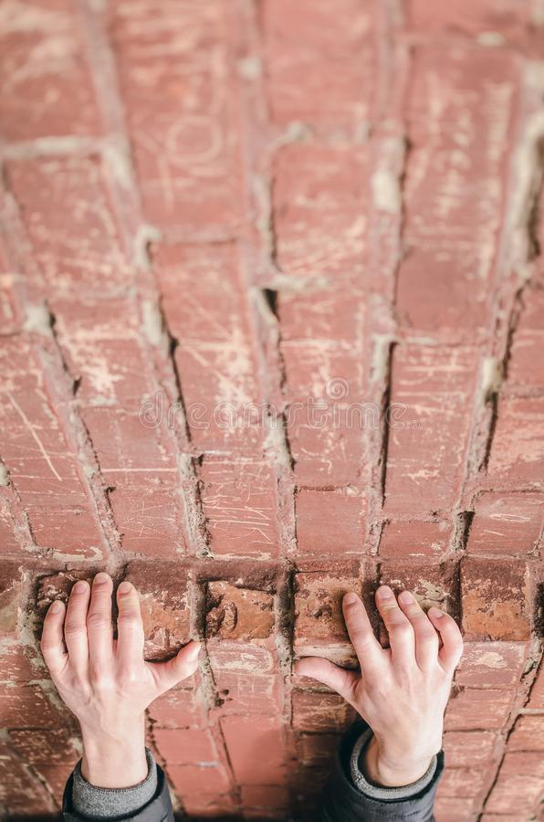 Fall. Man holds onto a ledge on a brick wall. A man holds onto a ledge on a brick wall so as not to fall down. The man climbs up. Person falling down royalty free stock photography