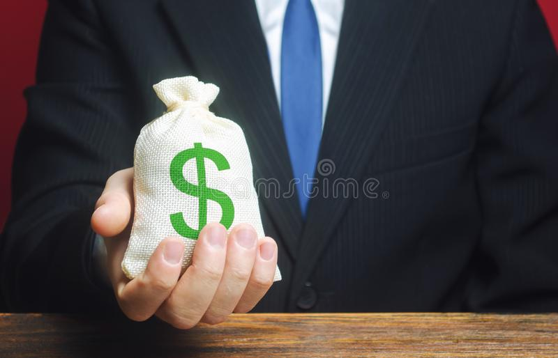 A man holds out a bag of money. Provision of money on credit, grant. Project financing. Donations. Financial social assistance. Payment purchases, profits stock photos