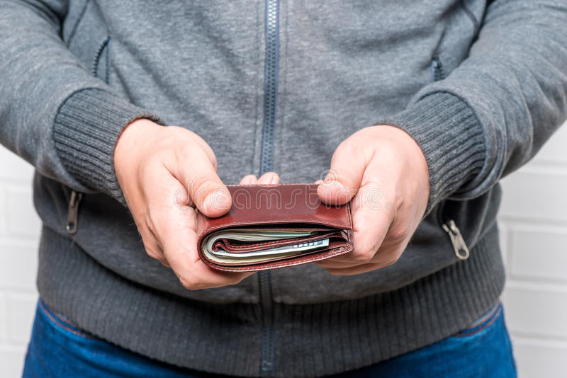 Man holds out his purse with money stock images