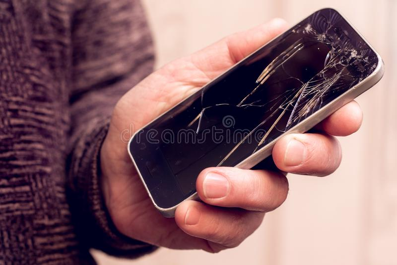 A man holds a phone with a broken glass in his hand. Phone repair service_. A man holds a phone with a broken glass in his hand. Phone repair service stock image