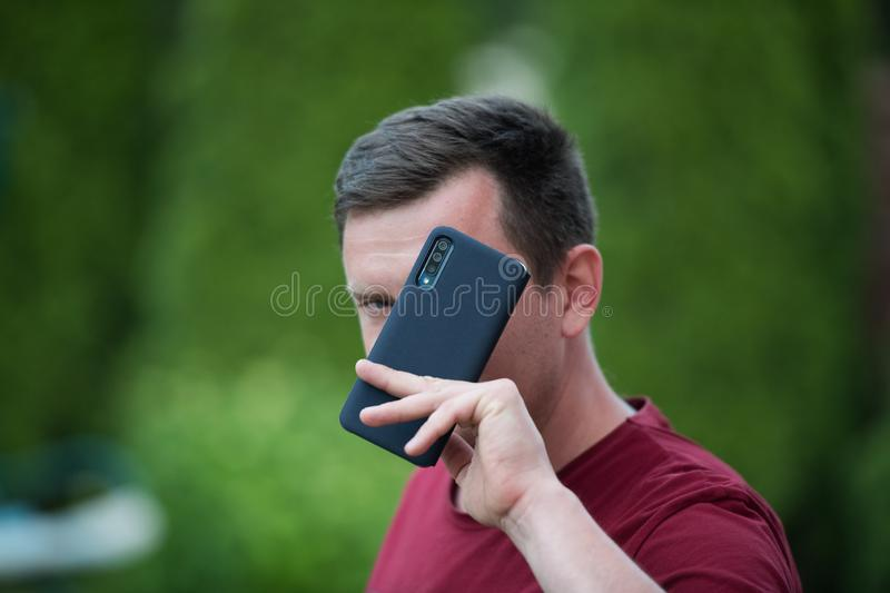 A man holds a phone in a protective case. phone safety from falling. bumper on the phone. dark phone. place to write. Smartphone. On blurred park background in stock image