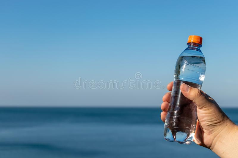 A man holds a plastic bottle of drinking water in his hand, standing on the ocean. A man holds a plastic bottle of drinking water in his hand stock photos