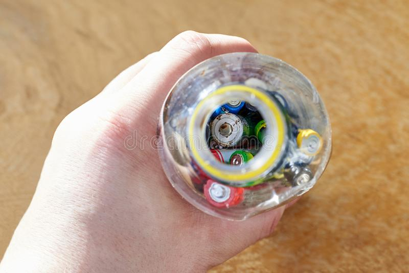 A man holds a plastic bottle with used batteries, the topic of sorting garbage stock image