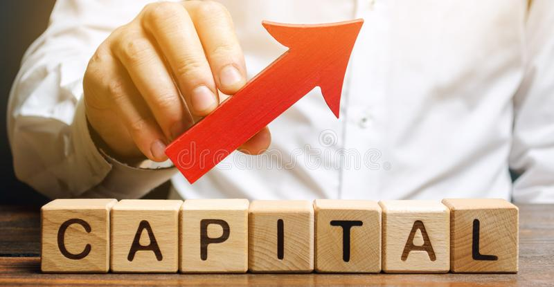 Man holds red arrow up above word Capital. Increase investment and foreign capital in the national economy. Improve business. Climate and increase royalty free stock image