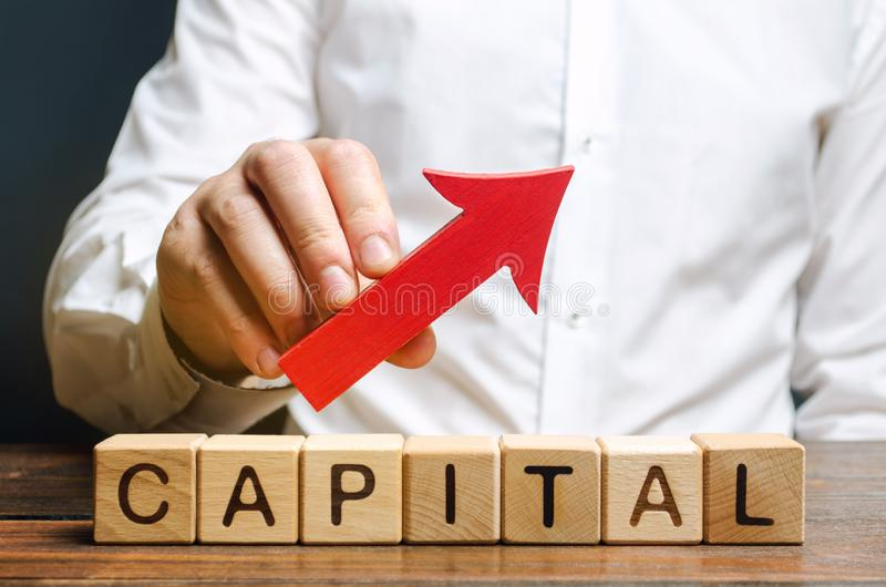 Man holds red arrow up above word Capital. Increase investment and foreign capital in the national economy. Improve business. Climate and increase stock photography