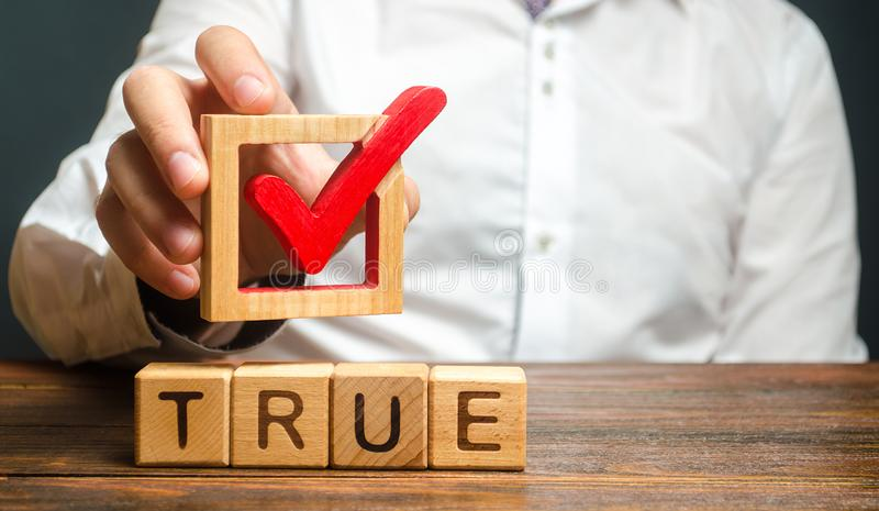 A man holds a red check mark over word True. Confirm the veracity and truth. Fight against fake news hostile propaganda. Confirmation facts, refutation of royalty free stock photo