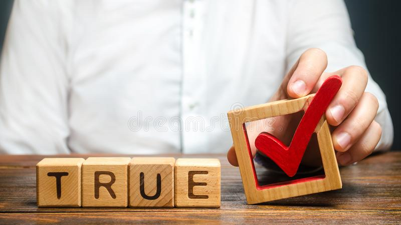 A man holds a red check mark over word True. Confirm the veracity and truth. Fight against fake news hostile propaganda. Confirmation facts, refutation of royalty free stock photography