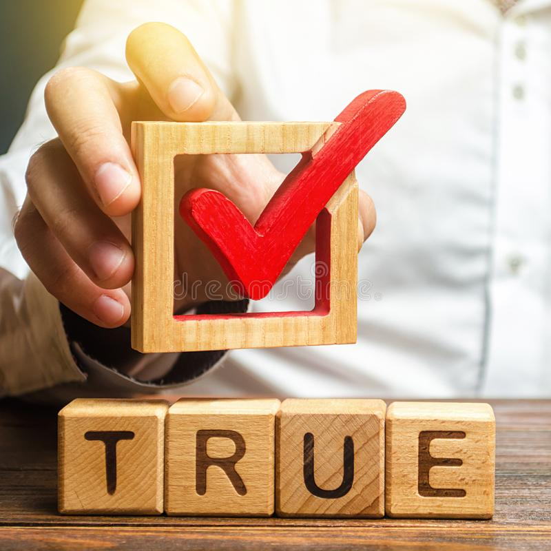 A man holds a red check mark over word True. Confirm the veracity and truth. Fight against fake news hostile propaganda. Confirmation facts, refutation of stock image