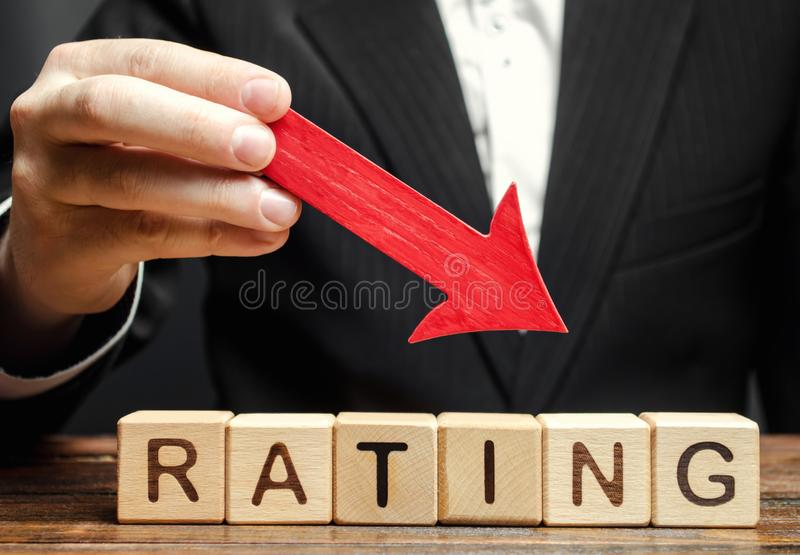 A man holds a red down arrow above the word Rating. The concept of deteriorating restaurant rating. Bad feedback. Low or negative. Quality of service. Review of stock photos