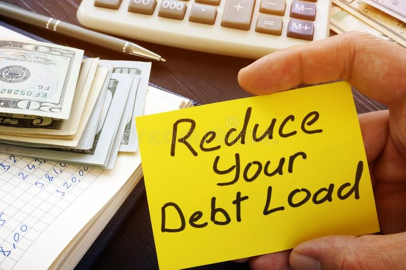 Man holds Reduce your debt load sign. Man holds Reduce your debt load inscription stock images