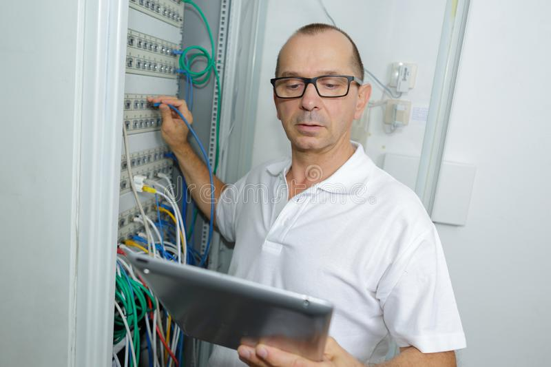 Man holds server cables while checking tablet stock photos