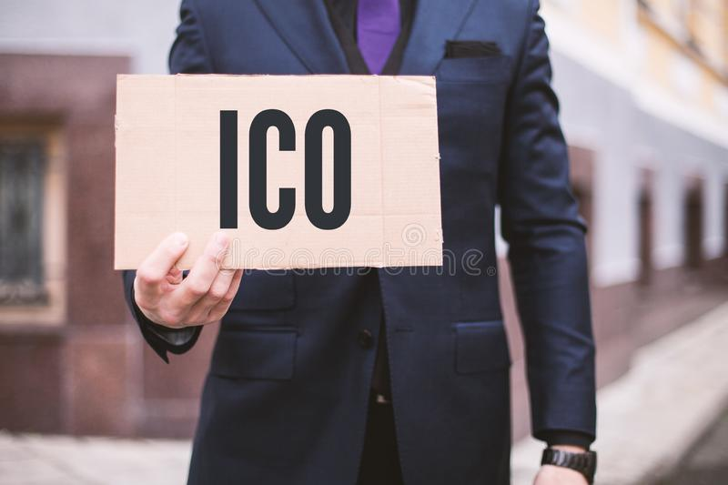 The man holds a sign in his hand with the inscription `ICO` Initial Coin Offerering. Digital Electronic Trade Market Stock Ind royalty free stock photography