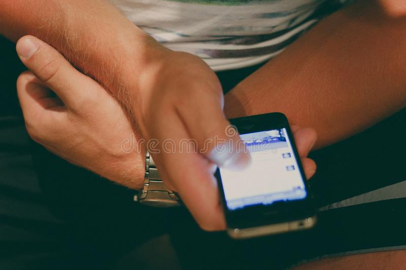Man holds a smartphone in his hand and watches a news line royalty free stock photo
