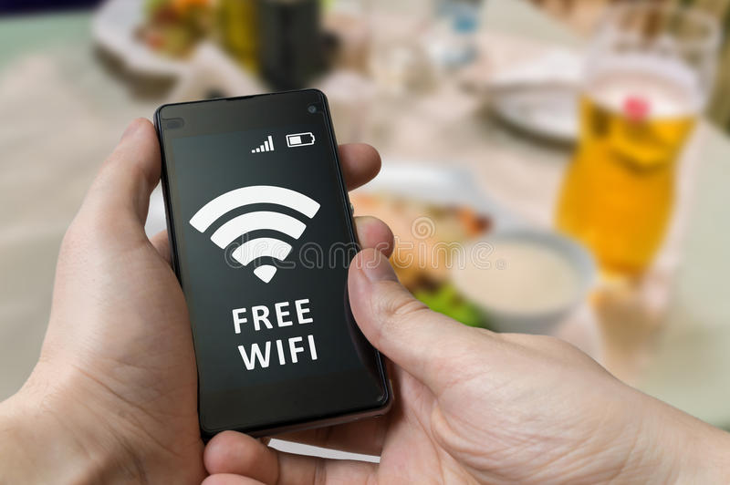 Man holds smartphone and is using free wifi in restaurant.  royalty free stock image