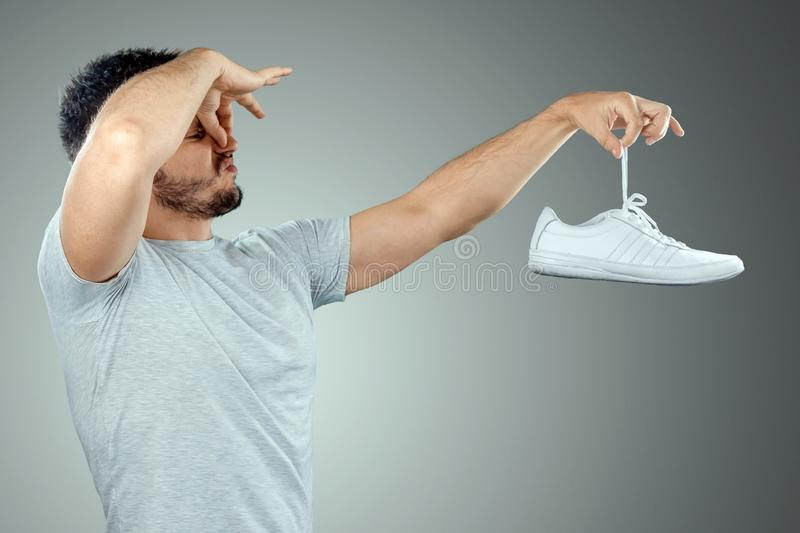 A man holds sneakers in his hands. Nasty smell. Stink legs, fungus on the legs.  stock images