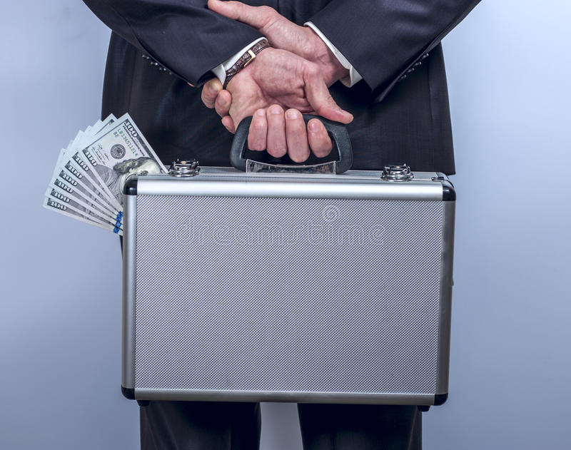 Man holds a suitcase with money behind the back stock photos