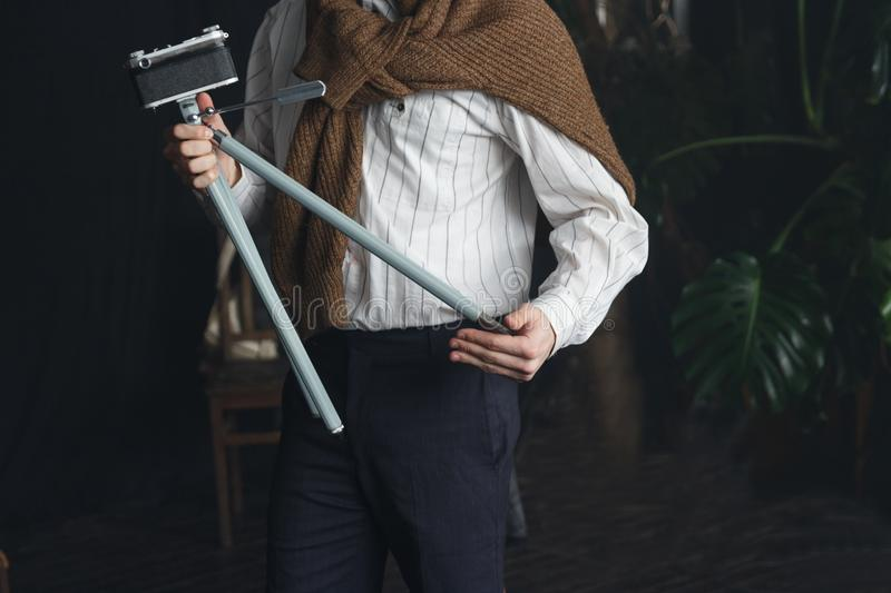 a man in a white shirt and a brown sweater is holding an old tripod with a camera, a vintage stock photography