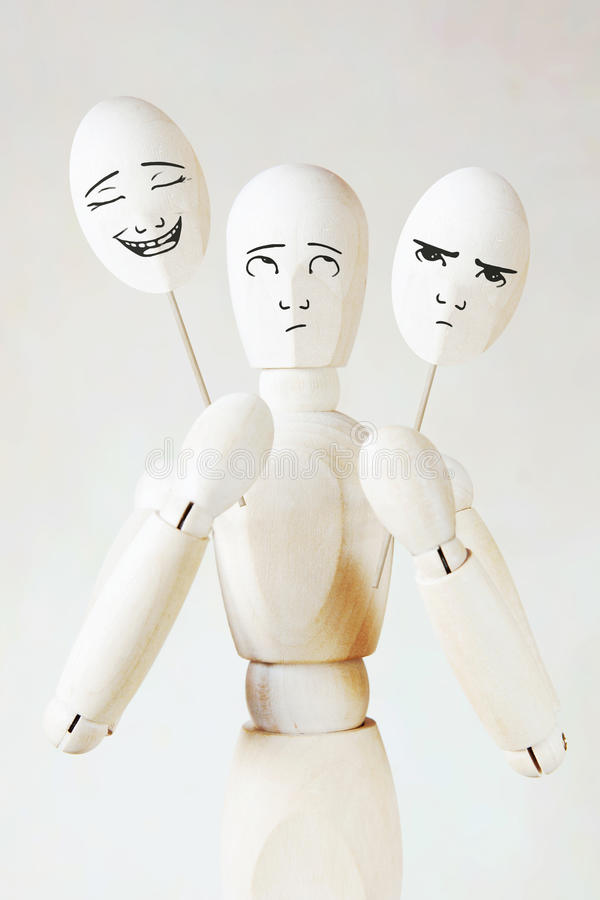 Man holds two masks with different mood. Abstract image with a wooden puppet stock images