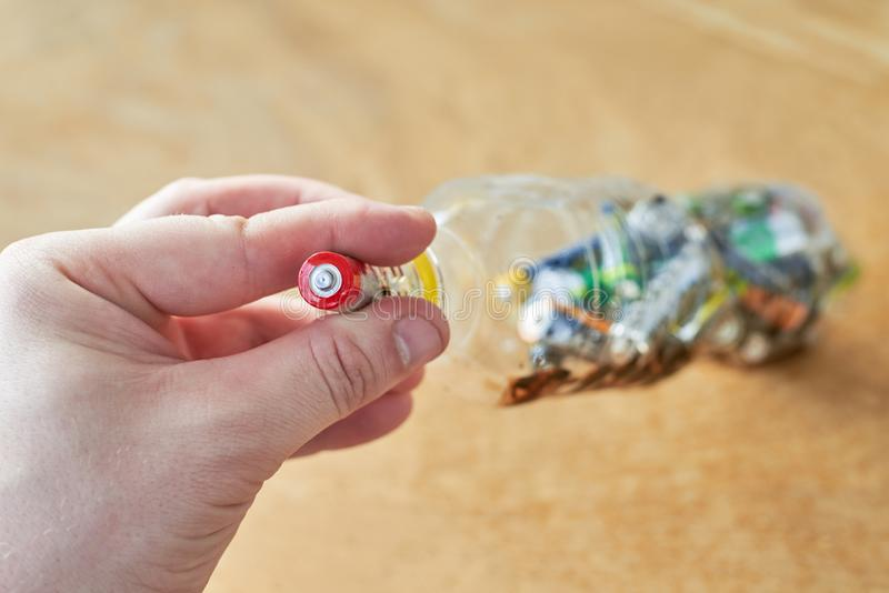A man holds used batteries to throw in a plastic bottle, the topic of sorting garbage stock photo