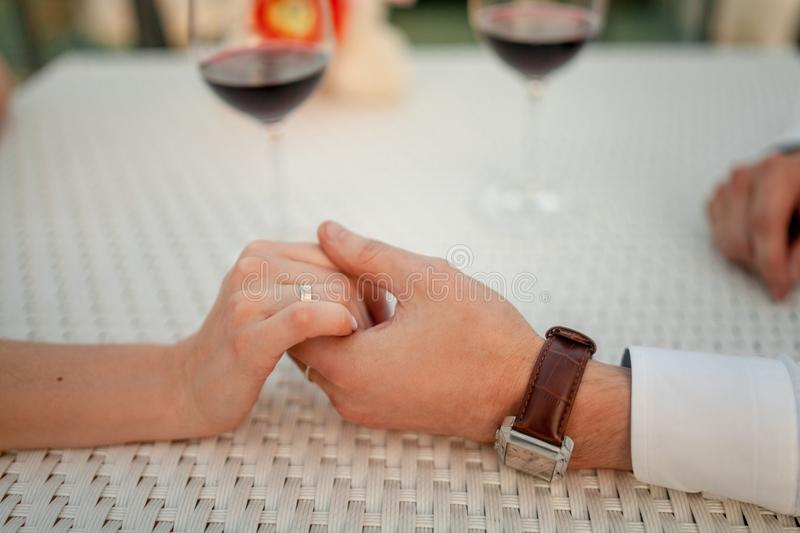 Man holds woman`s hand in cafe on background of wineglasses. Closeup. royalty free stock image