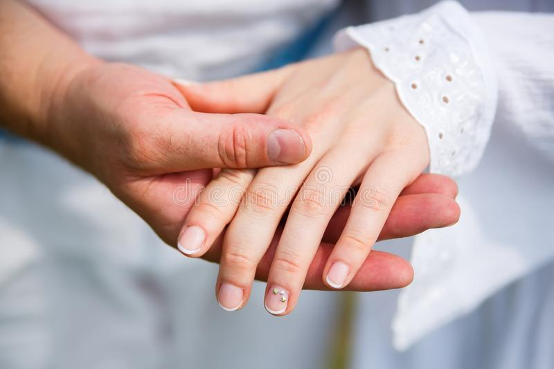 Man holds a womans hand in his palm. On a white background stock photos