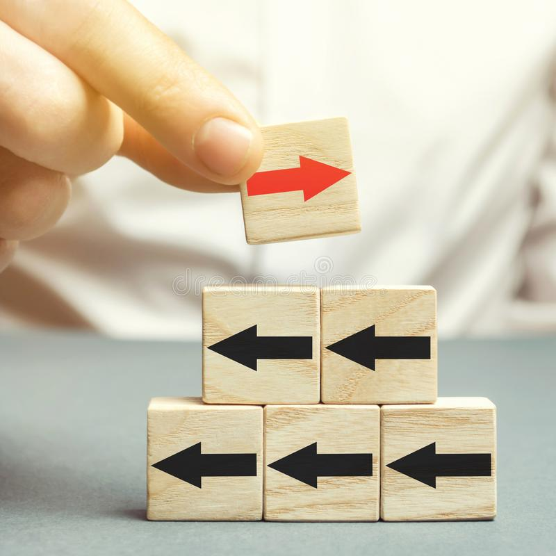 A man holds a wooden block with red arrow facing the opposite direction black arrows. Individual opinion. Stand out from the crowd. Uniqueness. Divergent views stock images