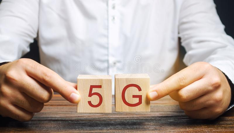 A man holds wooden blocks with the word 5G. High-speed mobile Internet. New generation networks. Fifth generation cellular network royalty free stock image