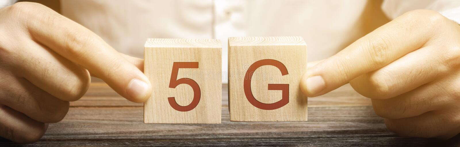 A man holds wooden blocks with the word 5G. High-speed mobile Internet. New generation networks. Fifth generation cellular network. Technology stock photo