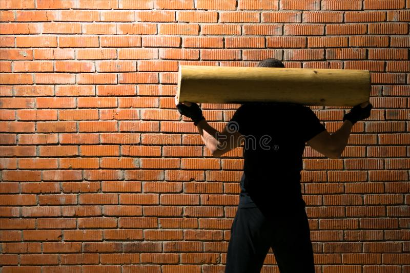 Man holds a wooden log on his back, doing sports in the hall with a left on the painting wall an empty space for your inscription. Man holds a wooden log on his royalty free stock photography