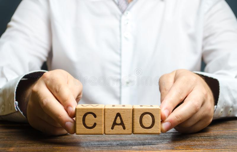 Man holds the word CAO in hands. Chief Accounting Officer. Vacancy and duties of a specialist. Manage taxes and payroll. Develop royalty free stock photography