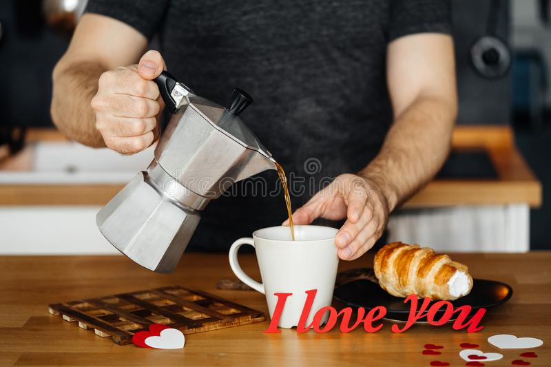 Man in home clothes pours hot coffee into a mug with the words I LOVE YOU from red paper on the table with a cake, against the bac stock photography