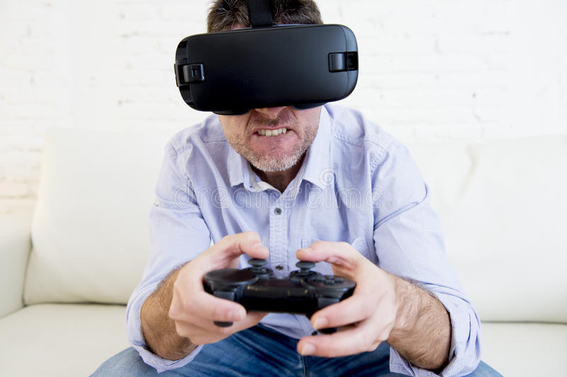 Man at home living room sofa couch excited using 3d goggles play. Young modern man at home living room sofa couch playing video game excited using 3d goggles stock photos