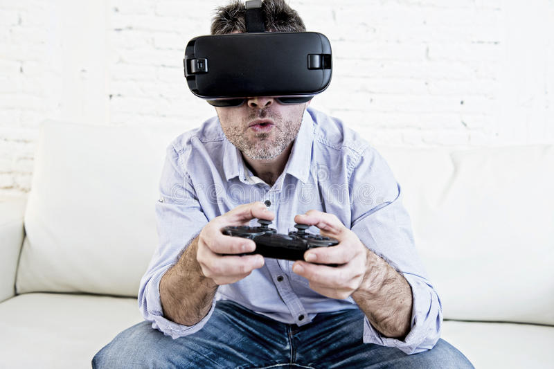 Man at home living room sofa couch excited using 3d goggles play. Young modern man at home living room sofa couch playing video game excited using 3d goggles royalty free stock photography