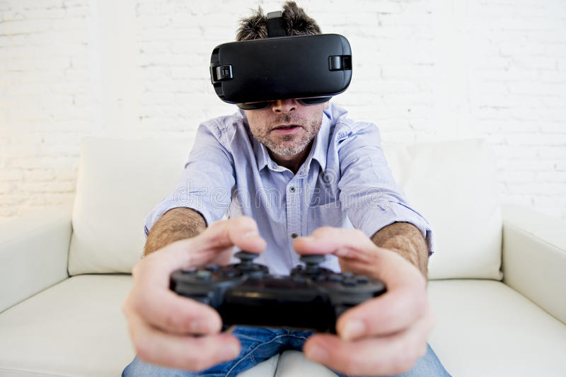 Man at home living room sofa couch excited using 3d goggles play. Young modern man at home living room sofa couch playing video game excited using 3d goggles royalty free stock images