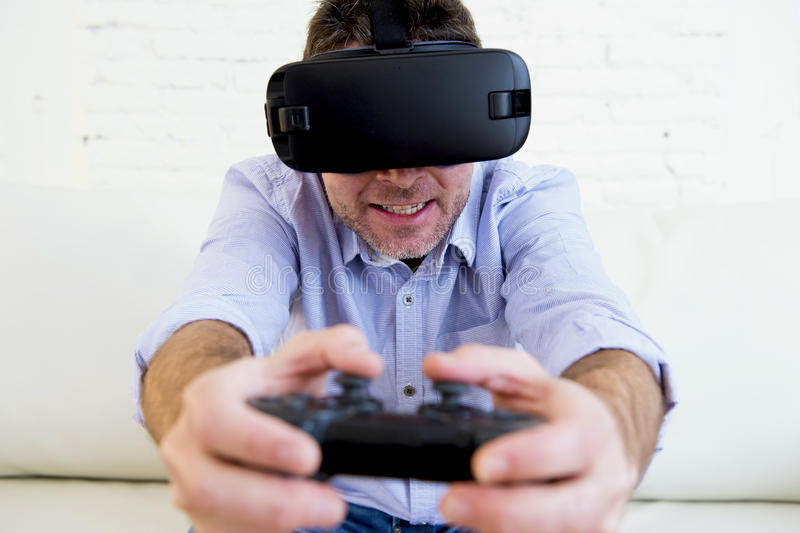 Man at home living room sofa couch excited using 3d goggles play. Young modern man at home living room sofa couch playing video game excited using 3d goggles stock images
