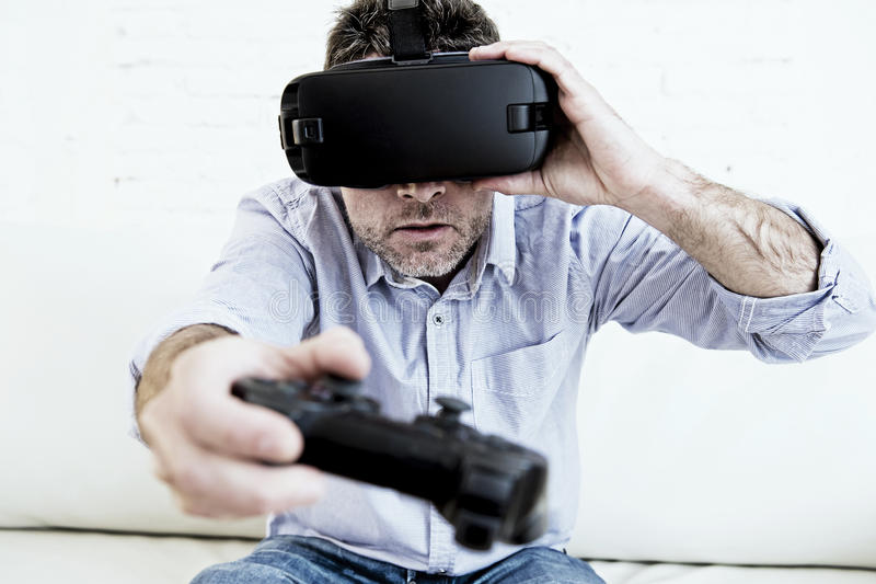 Man at home living room sofa couch excited using 3d goggles play. Young modern man at home living room sofa couch playing video game excited using 3d goggles royalty free stock photos