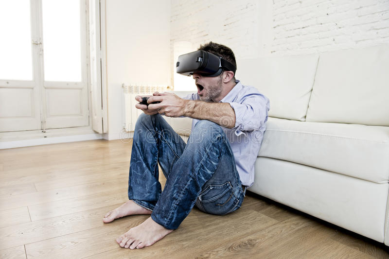 Man at home living room sofa couch excited using 3d goggles play. Young modern man at home living room sofa couch playing video game excited using 3d goggles royalty free stock photo