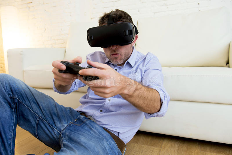 Man at home living room sofa couch excited using 3d goggles play. Young modern man at home living room sofa couch playing video game excited using 3d goggles stock photography