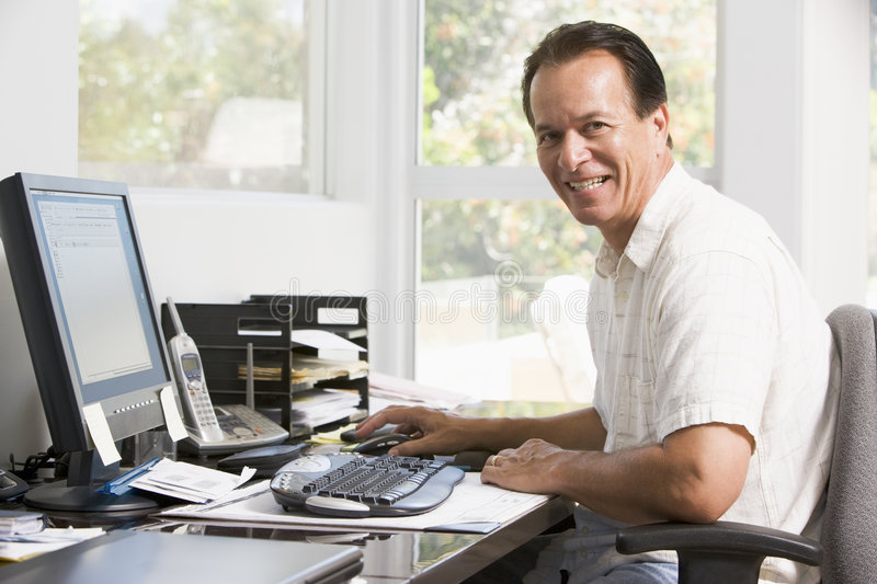 Man In Home Office At Computer Smiling Stock Photo