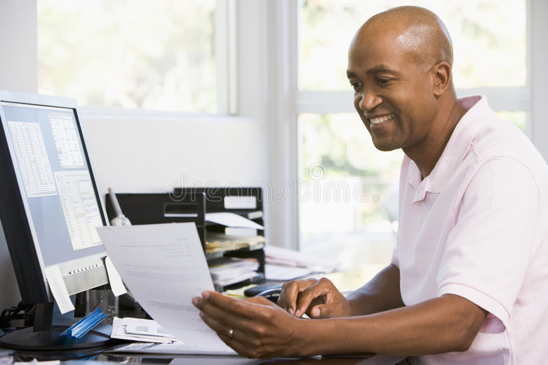 Man in home office using computer and smiling stock image