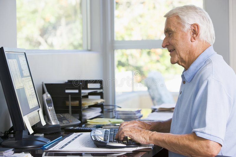 Man in home office using computer smiling stock photography
